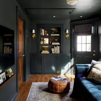 Example of a mid-sized transitional enclosed medium tone wood floor, brown floor and wainscoting living room library design in Detroit with black walls, no fireplace and a wall-mounted tv
