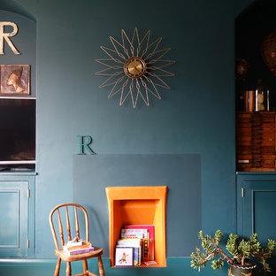 Ejemplo de salón abierto, bohemio, grande, sin chimenea, con suelo de madera en tonos medios, marco de chimenea de yeso, televisor independiente y paredes azules