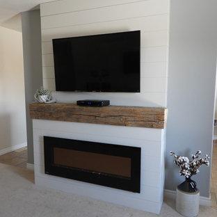 Inspiration för mellanstora lantliga separata vardagsrum, med grå väggar, heltäckningsmatta, en hängande öppen spis, en spiselkrans i trä, en väggmonterad TV och beiget golv