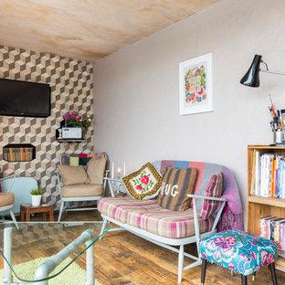 Inspiration för ett litet eklektiskt vardagsrum, med ett bibliotek, mellanmörkt trägolv och en väggmonterad TV