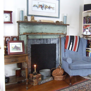 Photo of a romantic living room in Other with a reading nook, white walls and a standard fireplace.
