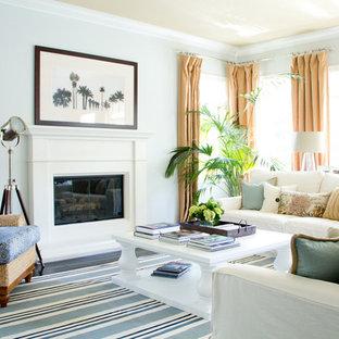 Ispirazione per un soggiorno tropicale di medie dimensioni con pareti grigie, camino classico, cornice del camino in intonaco e nessuna TV