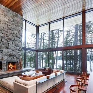 Réalisation d'un très grand salon chalet ouvert avec un sol en bois foncé, une cheminée standard, un manteau de cheminée en pierre, un sol marron et un plafond en bois.