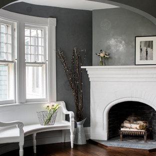 Ejemplo de salón tradicional con paredes grises, suelo de madera oscura, marco de chimenea de ladrillo y chimenea de esquina