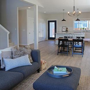 Idee per un grande soggiorno stile americano aperto con pareti grigie, pavimento in vinile, camino classico, cornice del camino piastrellata e nessuna TV
