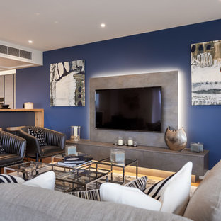 Design ideas for a contemporary living room in Dorset with blue walls and a wall mounted tv.