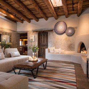 アルバカーキのサンタフェスタイルのおしゃれな独立型リビング (マルチカラーの壁、コーナー設置型暖炉、漆喰の暖炉まわり、壁掛け型テレビ、茶色い床) の写真
