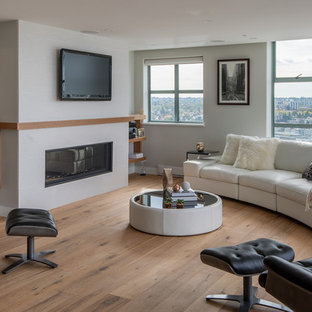 Example of a large trendy open concept medium tone wood floor and brown floor living room design in Vancouver with a ribbon fireplace, a wall-mounted tv, a tile fireplace and gray walls