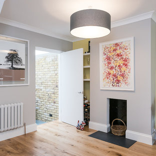 Design ideas for a medium sized contemporary formal open plan living room in London with brown walls, light hardwood flooring, a standard fireplace, a metal fireplace surround, a freestanding tv and yellow floors.