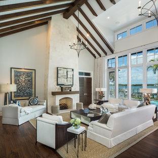 Imagen de salón para visitas abierto, contemporáneo, extra grande, sin televisor, con paredes beige, suelo de madera oscura, chimenea tradicional y marco de chimenea de piedra