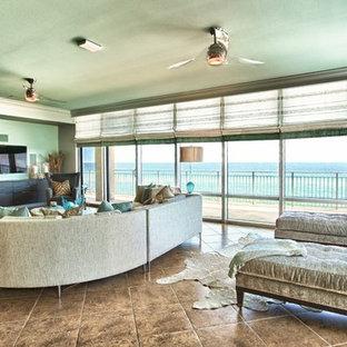 Ejemplo de salón costero con paredes verdes y televisor colgado en la pared
