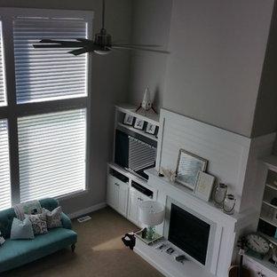 Ispirazione per un grande soggiorno stile marinaro con pareti grigie, moquette, camino classico, cornice del camino in legno e TV a parete