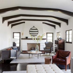 ロサンゼルスの地中海スタイルのおしゃれな独立型リビング (フォーマル、白い壁、濃色無垢フローリング、標準型暖炉、タイルの暖炉まわり、テレビなし) の写真
