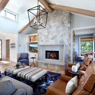 Example of a huge coastal open concept light wood floor living room design in Grand Rapids with gray walls, a standard fireplace, a stone fireplace and a media wall