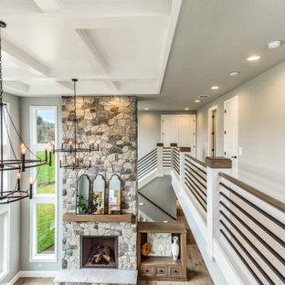 Bild på ett stort vintage allrum med öppen planlösning, med grå väggar, ljust trägolv, en standard öppen spis, en spiselkrans i sten, en inbyggd mediavägg och grått golv