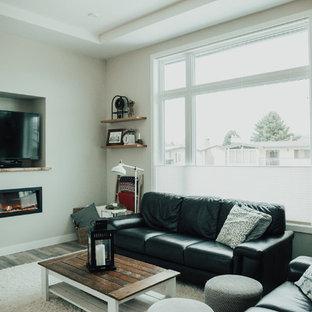 Immagine di un soggiorno industriale di medie dimensioni e aperto con pareti grigie, pavimento in vinile, camino sospeso e parete attrezzata