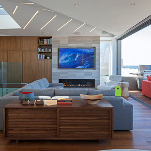 This is an example of a medium sized contemporary open plan living room in Los Angeles with brown walls, dark hardwood flooring, a ribbon fireplace, a stone fireplace surround, a wall mounted tv and brown floors.