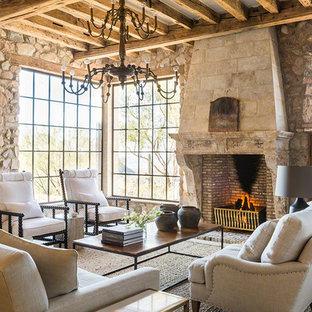Cette image montre un salon méditerranéen avec une salle de réception, un mur multicolore, un sol en calcaire, une cheminée standard, un manteau de cheminée en pierre et un sol beige.