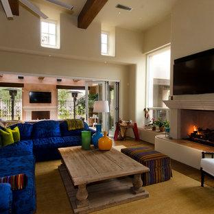 Esempio di un soggiorno stile americano di medie dimensioni e aperto con pareti beige, pavimento in legno massello medio, camino classico, cornice del camino in intonaco, TV a parete e pavimento marrone