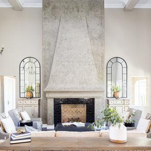 フェニックスの地中海スタイルのおしゃれなリビング (無垢フローリング、タイルの暖炉まわり、ベージュの壁、標準型暖炉、テレビなし、茶色い床) の写真