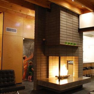 Immagine di un piccolo soggiorno moderno aperto con pareti grigie, pavimento in cemento, camino bifacciale, cornice del camino in cemento e TV a parete