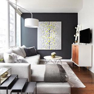 Esempio di un piccolo soggiorno minimalista stile loft con pareti bianche, pavimento in legno massello medio, nessun camino, TV a parete e pavimento marrone