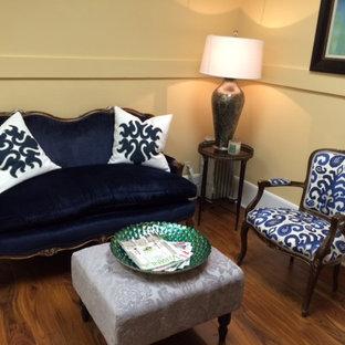 Foto di un piccolo soggiorno eclettico chiuso con angolo bar, pareti gialle, pavimento in legno massello medio, nessun camino e nessuna TV