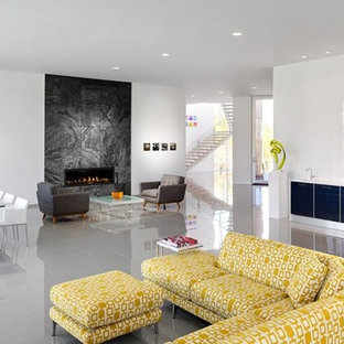 Huge trendy open concept porcelain floor living room photo in Detroit with a bar, white walls, a standard fireplace, a stone fireplace and no tv