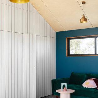 Nordisches Wohnzimmer mit blauer Wandfarbe, Teppichboden, grauem Boden, Holzdielendecke und Wandpaneelen in Melbourne