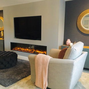 Inspiration for a medium sized contemporary formal enclosed living room in Buckinghamshire with grey walls, carpet, a standard fireplace, a plastered fireplace surround, a built-in media unit and grey floors.