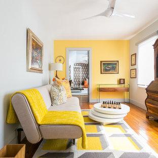 Diseño de salón para visitas abierto, bohemio, de tamaño medio, sin chimenea y televisor, con paredes amarillas, suelo de madera en tonos medios y suelo marrón
