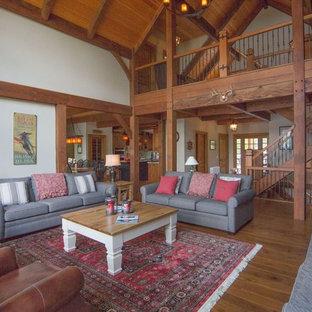 Immagine di un grande soggiorno stile americano aperto con pareti beige, pavimento in legno massello medio, camino classico, cornice del camino in pietra e TV a parete