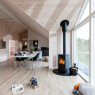 Ejemplo de salón para visitas abierto, nórdico, de tamaño medio, con suelo de madera clara, paredes beige y estufa de leña