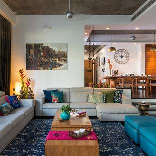 Immagine di un soggiorno etnico aperto e di medie dimensioni con pareti bianche, pavimento nero e pavimento in cemento
