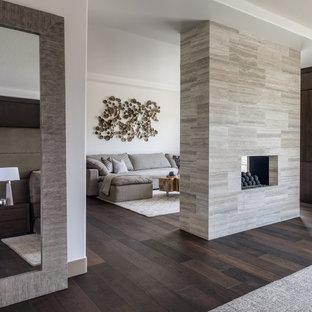 Ispirazione per un ampio soggiorno design con sala formale, pareti bianche, parquet scuro, camino bifacciale, cornice del camino piastrellata e pavimento marrone