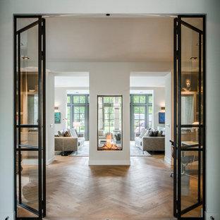 Diseño de salón para visitas abierto, actual, grande, sin televisor, con paredes blancas, suelo de madera en tonos medios, chimenea de doble cara, marco de chimenea de yeso y suelo marrón
