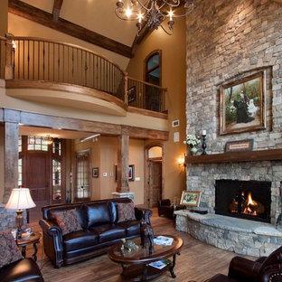 Ejemplo de biblioteca en casa abierta, rústica, extra grande, con marco de chimenea de piedra, paredes marrones, suelo de madera en tonos medios, chimenea tradicional, pared multimedia y suelo marrón