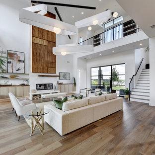 Ejemplo de salón abierto, contemporáneo, con paredes blancas, suelo de madera en tonos medios, chimenea lineal y suelo marrón