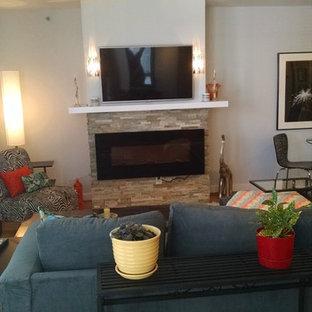 Idee per un grande soggiorno classico aperto con pareti grigie, pavimento in bambù, camino sospeso, cornice del camino in pietra e TV a parete