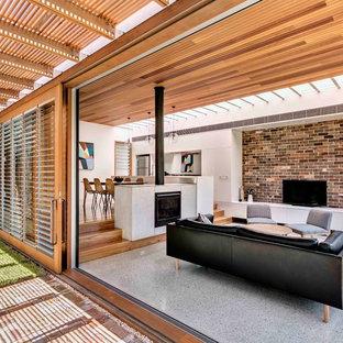 Ejemplo de salón abierto, minimalista, de tamaño medio, con suelo de cemento, chimenea tradicional y televisor independiente