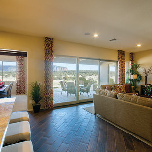 Living room in Phoenix with yellow walls, a wall mounted tv and brown floors.