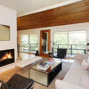 Idéer för att renovera ett mellanstort allrum med öppen planlösning, med ett finrum, vita väggar, ljust trägolv, en standard öppen spis, en spiselkrans i tegelsten och beiget golv