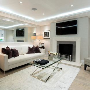 Living room - contemporary formal light wood floor living room idea in London with gray walls, a standard fireplace and a wall-mounted tv