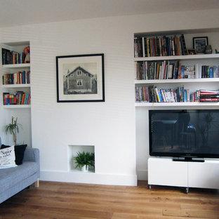 Idee per un soggiorno minimal di medie dimensioni e aperto con libreria, pareti bianche, nessun camino, cornice del camino in intonaco e parete attrezzata