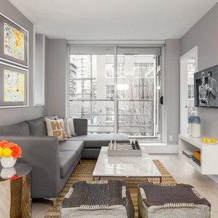 Immagine di un soggiorno design di medie dimensioni e aperto con pareti grigie, nessun camino, TV a parete, sala formale e pavimento in laminato