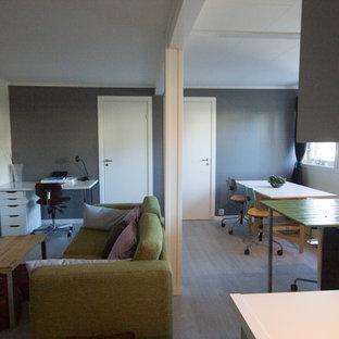 Imagen de salón abierto, escandinavo, pequeño, con paredes blancas, suelo laminado, estufa de leña, marco de chimenea de metal, televisor independiente y suelo gris
