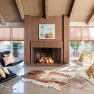 ロサンゼルスの広いモダンスタイルのおしゃれなLDK (フォーマル、白い壁、標準型暖炉、レンガの暖炉まわり、大理石の床、白い床) の写真
