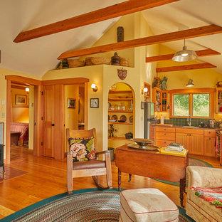Ejemplo de salón abierto, rústico, con paredes amarillas, suelo de madera en tonos medios y estufa de leña