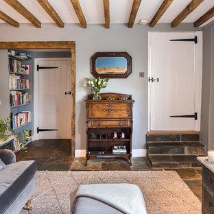 Idee per un soggiorno country di medie dimensioni con pareti grigie, pavimento in ardesia, stufa a legna, cornice del camino in mattoni e pavimento grigio