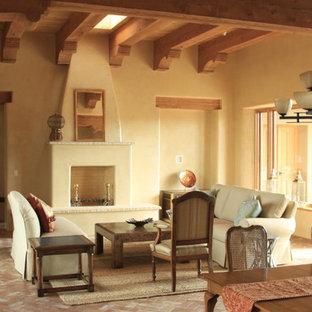 Großes, Repräsentatives, Fernseherloses, Offenes Mediterranes Wohnzimmer mit beiger Wandfarbe, Backsteinboden, Kamin, Kaminsims aus Beton und braunem Boden in Albuquerque